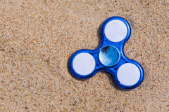 Spinner toy. Good quality photo of a truly popular game - the spinner! Photo shows spinner toy. Yellow sand background, true colors and light conditions. Fits Royalty Free Stock Photography