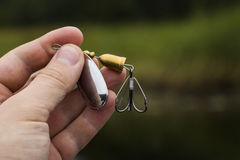 Spinner with a triple hook for fishing. In the hand Stock Images