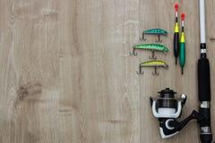Spinnerlokmiddelen, visserijbytes, vlotters, spinnende spoel en staaf op hout Plaats voor tekst stock foto's