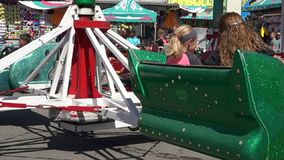 Spinning, Amusement Park Rides, Fun, Leisure. Stock video of spinning rides. Girl with long blonde hair stock footage