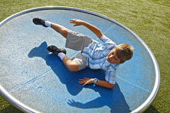 Spinning Around. Boy spinning on a turn table in the park Stock Photos