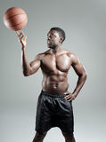 Spinning basketball. Muscular black sportsman spins a basketball topless Royalty Free Stock Photo