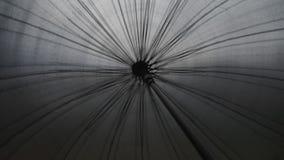 Spinning black umbrella. In the rain stock footage