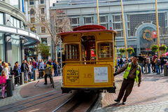 Spinning the Cable Car. Tourists watch as a San Francisco cable car is spun around on a turntable Royalty Free Stock Photo
