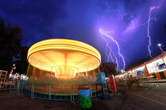 Spinning carousel in motion with thunderstorm Stock Image