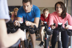 Spinning class on exercise bikes at a gym, close up Royalty Free Stock Images