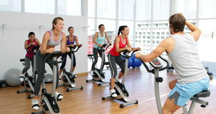 Spinning class in fitness studio led by energetic instructor stock footage
