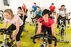Spinning class people at the fitness center. Spinning class people at the gym enjoy physical workout Stock Image