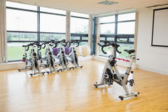 Spinning exercise bikes in gym room Stock Images
