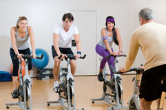 Spinning exercises with instructor. Fitness instructor with his class of spinning cycler at gym Stock Image
