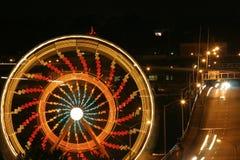Spinning Ferris Wheel. A Ferris Wheel spinning near a busy bridge in Portland, Oregon Royalty Free Stock Image