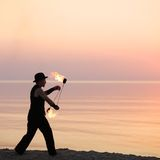 Spinning fire poi on the beach Stock Image