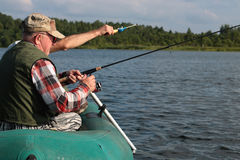 Spinning fisherman on a boat fishing Royalty Free Stock Images