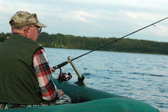 Spinning fisherman on a boat fishing Royalty Free Stock Photos