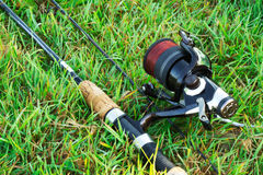 Spinning fishing on the green grass by the river. Royalty Free Stock Photos