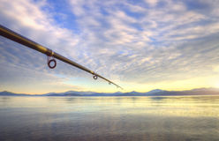 Spinning - fishing rod on the summer lake Royalty Free Stock Photos