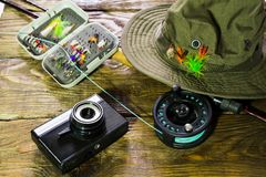 Spinning, fly fishing, flies, spinners, hat, camera for photographing the trophies and frame for your label lying on a wooden tabl. Spinning, fly fishing on a royalty free stock photo