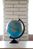 Spinning Globe.Earth globe on a brick wall background. Stock Photo