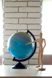 Spinning Globe. Earth globe on a brick wall background. Wooden man points at the globe Royalty Free Stock Images