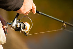 Spinning in the hands of the angler Stock Photography