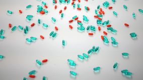 Spinning blue and orange pills over white studio background - above angle view. Spinning medicine over white cyc background modern stock video footage