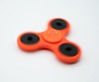 Spinning orange fidget spinner Royalty Free Stock Photography