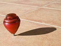 Spinning Red Top. Red top spinning on its axis, with the sun casting its shadow on the pavement Royalty Free Stock Images