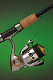 Spinning reel and a cork handled fishing pole. Spinning reel attached to a cork handled fishing pole on a glowing green background stock photo