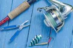 Spinning, reel, fishing green spoon and pliers. The bait and the tool of a fisherman. Fishing set Royalty Free Stock Photo