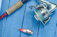 Spinning, reel, fishing lure yellow-red. The bait and the tool of a fisherman. Fishing reel Royalty Free Stock Images