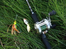 Spinning with reel on the grass. Spinning with reel and lure on the grass Stock Photography