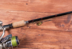 Spinning, reel and lure on a wooden background. Stock Photos