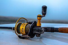 Spinning reel. Reel with a spinning rod spent the entire night and frozen. The first frost Royalty Free Stock Photo