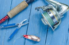 Spinning, reel, yellow-red fishing spoon and pliers. The bait and the tool of a fisherman. Fishing tool Royalty Free Stock Photography