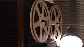 Spinning reels on an old tape recorder, recorded sound, light through the blinds.  stock video