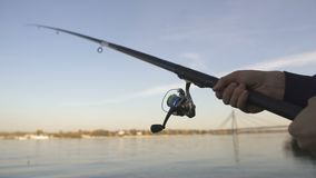 Spinning rod closeup, man fly-fishing near river, active leisure, weekend stock video