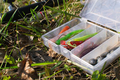 Spinning and set of baits on the grass. Evening fishing. Royalty Free Stock Image