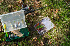 Spinning and set of baits on the grass. Evening fishing. Royalty Free Stock Photography