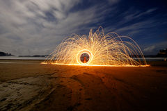 Spinning sparklers on the beach Stock Photography
