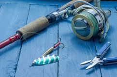 Spinning and spinning reel. Pliers. Spoon. Decorative background. Fishing set Royalty Free Stock Image
