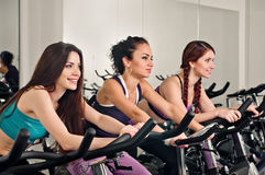 Spinning for three. Three spinning women in the fitness club stock photography