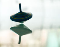 Spinning top in action on a mirror surface Royalty Free Stock Photo