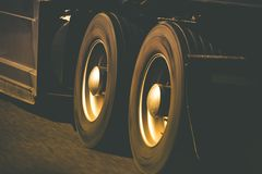 Spinning Truck Wheels. Spinning Semi Truck Wheels Closeup Photo. Browny Color Grading. Trucking and Transportation Theme royalty free stock image