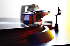 Spinning turntable. Turntable - needle on spinning record, colored light royalty free stock photo