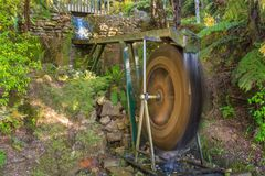 A spinning waterwheel in a scenic woodland setting stock photos