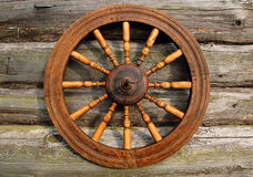 Spinning Wheel On The Log House Wall. Hand spinning wheel on the wall of the old log house in the Russian village Royalty Free Stock Image