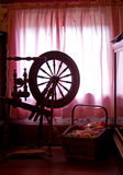 Spinning Wheel Silhouette. A d in front of pink curtains in a room with a basket of yarn stock photo