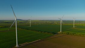 Spinning wind towers generating energy in fields. Drone view of wind turbines.