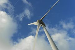 Spinning wind turbine on a cloudy day. Modern technology of electrical power generation. Renewable energy sources. Concept. Ecology and environmentally friendly Royalty Free Stock Photography