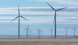 Spinning wind turbines on brown grassy plain Royalty Free Stock Photography